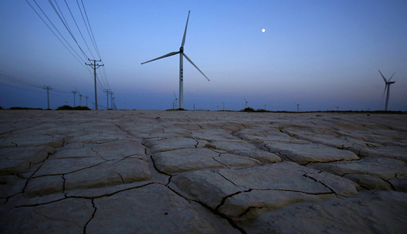 Cracked earth marks a dried-up area near a wind turbine used to generate electricity at a wind farm in Guazhou, 950km (590 miles) northwest of Lanzhou, Gansu Province